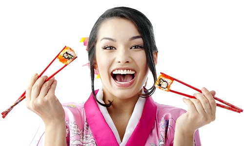 Happy Woman Eating Sushi with Two Pairs of Chopsticks.
